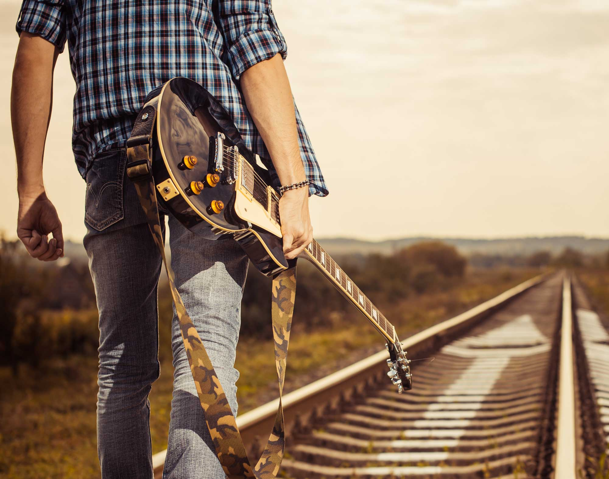 man walking down railroad track with guitar